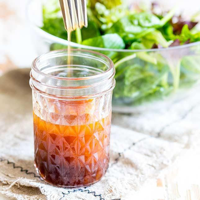 close up on a jar of sriracha salad dressing with a fork lifting out of it