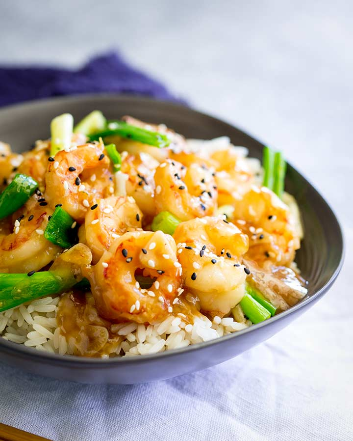 a grey bowl of ginger shrimp with rice and a white napkin