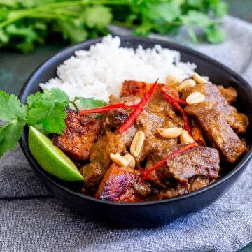 close up on a black bowl of Thai beef curry and rice
