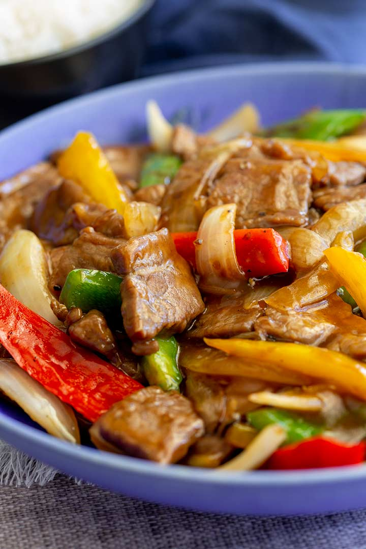 slices of beef and mixed pepper in a blue bowl.