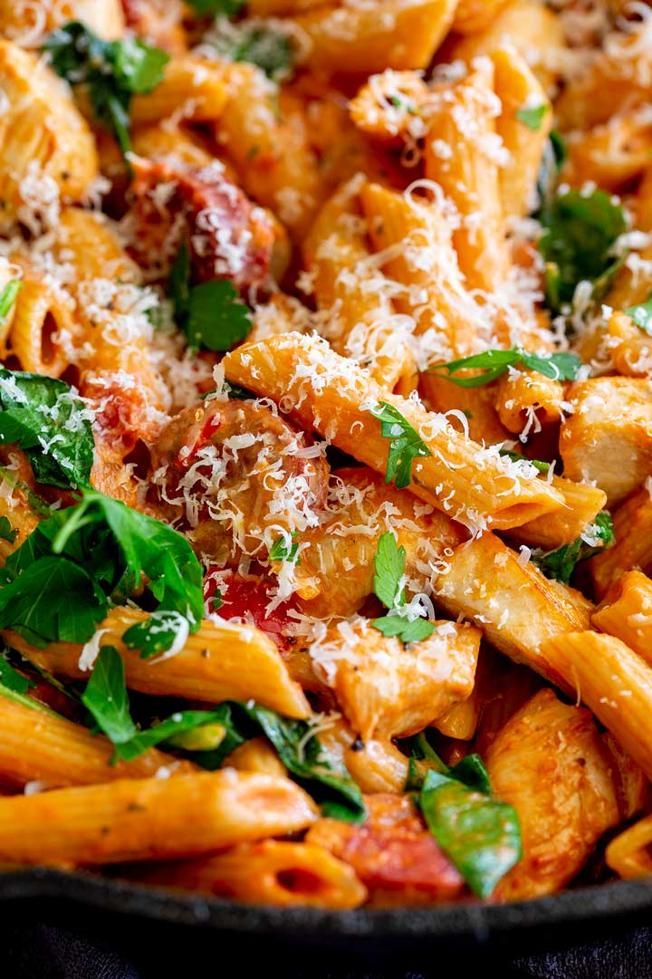 penne pasta in a creamy tomato sauce with parmesan and herbs on top