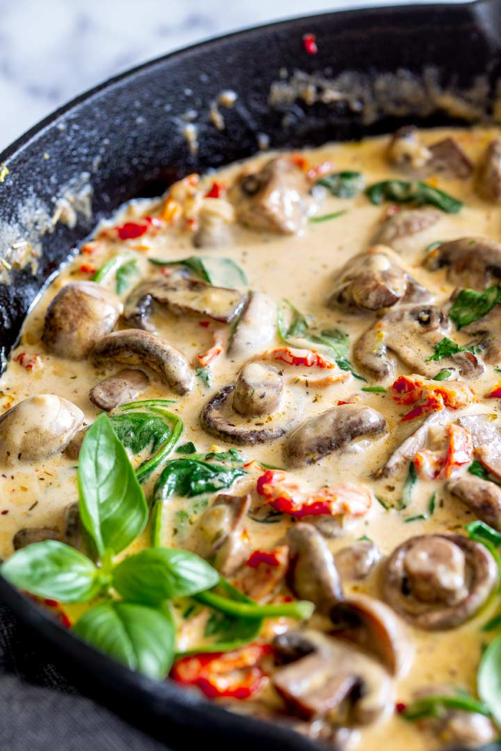 Skillet of creamy mushrooms with a basil sprig