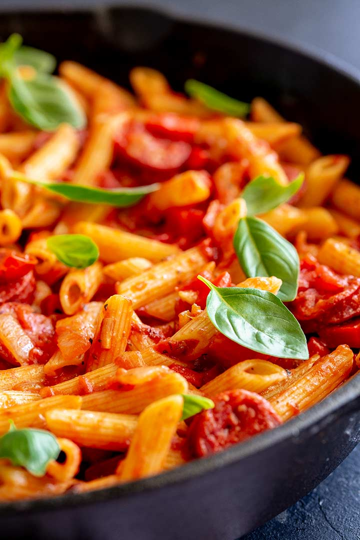 close up on the tomato penne in a pan garnished with fresh basil leaves