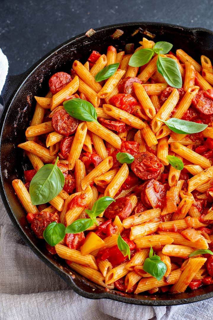 overhead view of a cast iron skillet filled with tomato and chorizo penne