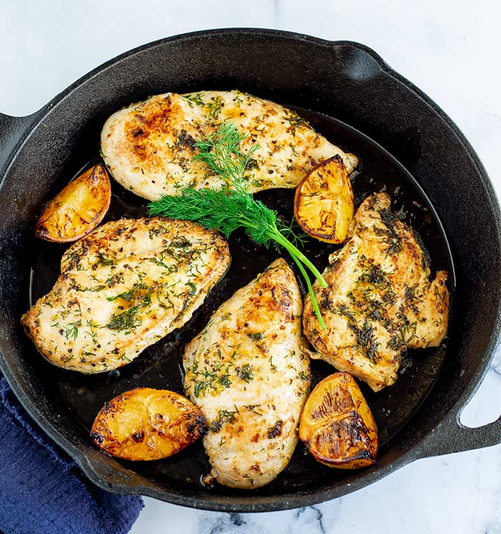 overhead view of a black skillet with four greek chicken breast, lemon and dill in it