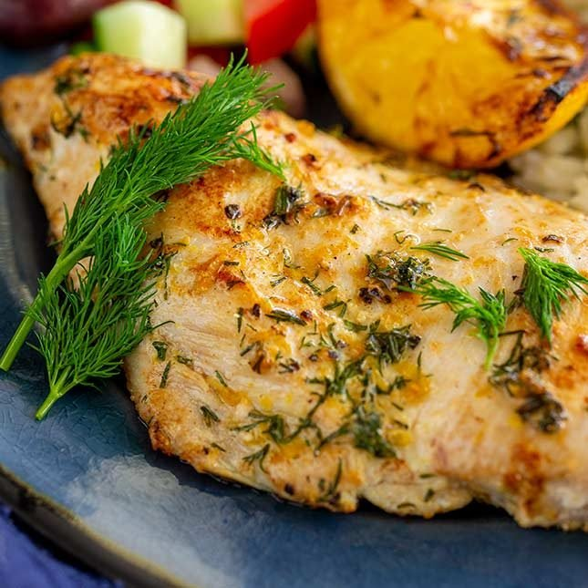 close up on a dill chicken breast on a blue plate