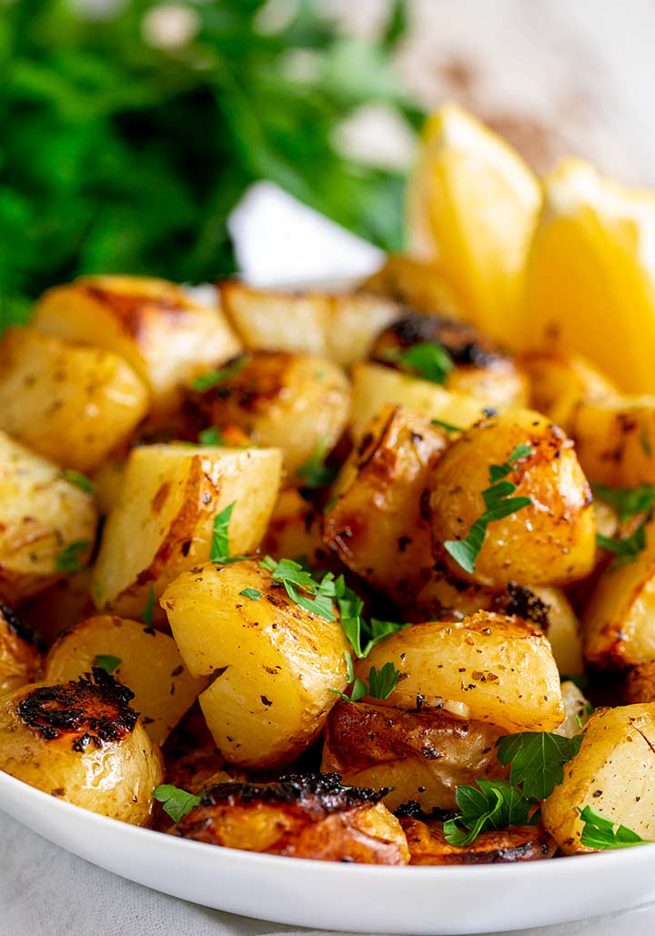 close up on greek potatoes in a white bowl with lemon and parsley
