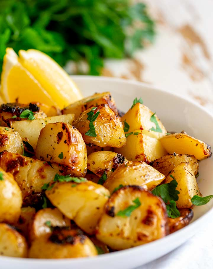 White bowl of cooked lemon potatoes on a rustic white table with herbs in the background