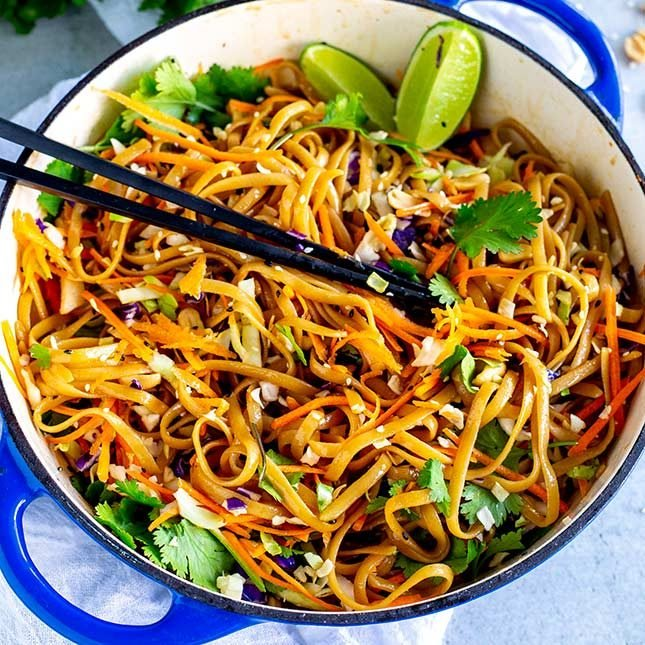 overhead view of a shallow blue pan of Thai noodles with chopsticks sticking in them