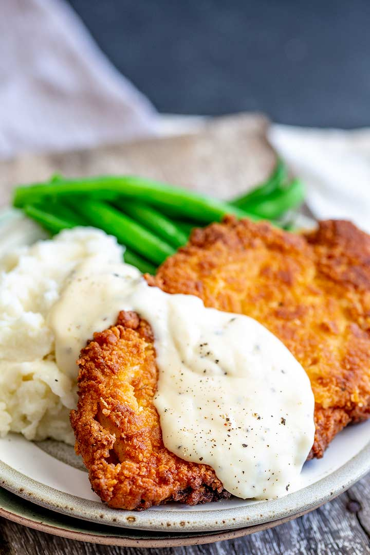mashed potato, green beans and fried chicken covered in white gravy