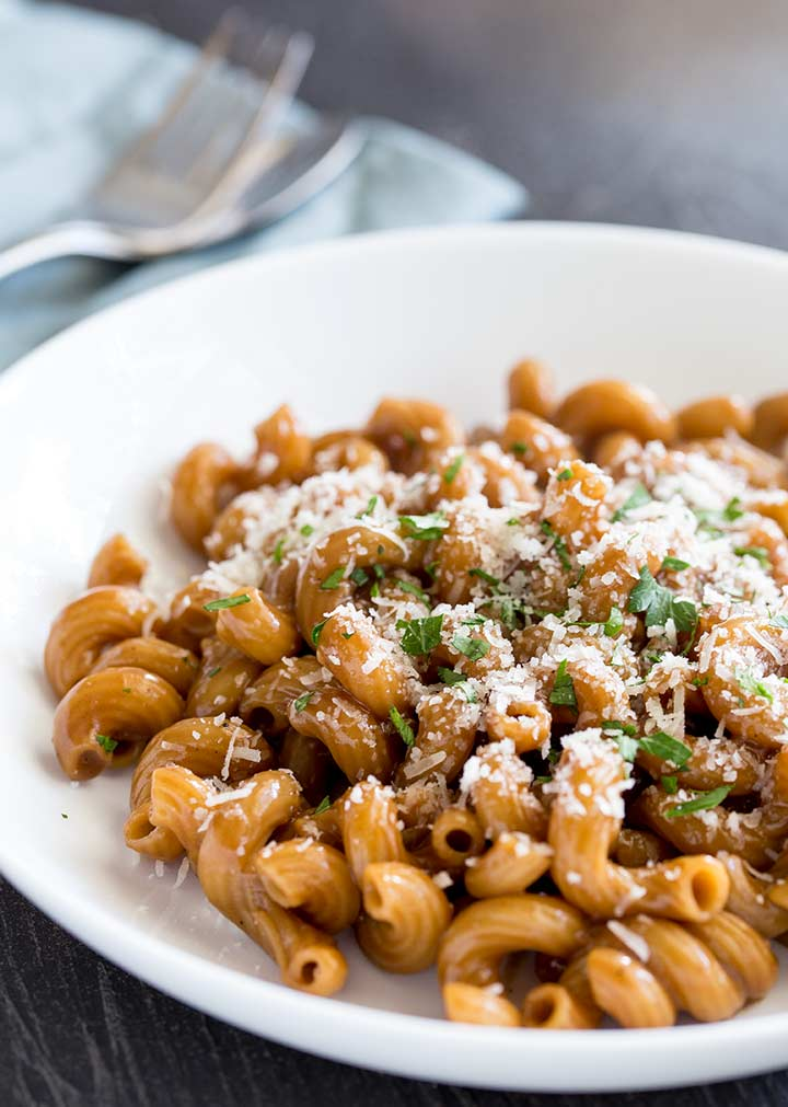 a white bowl of beef pasta on a black table garnished with parmesan and parsley