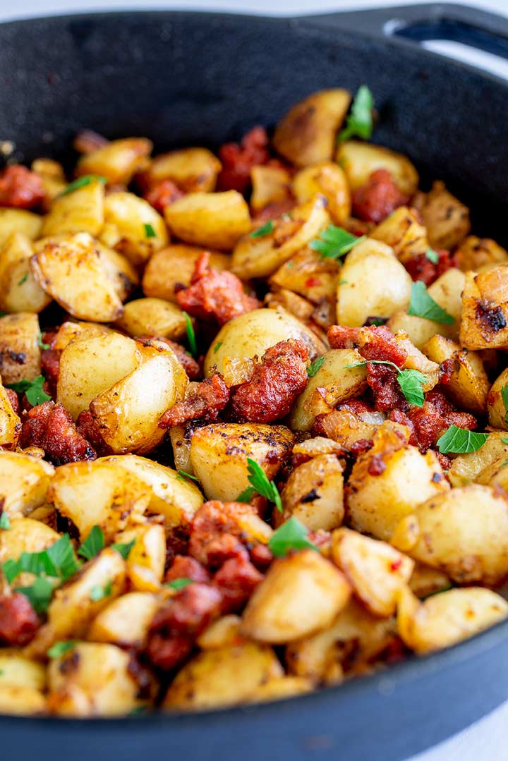 a black skillet filled with fried potatoes, chorizo and garnished with parsley