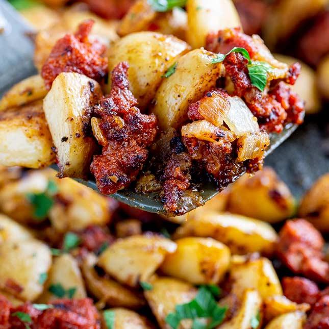 close up on a spatula lifting up chorizo and potato garnished with parsley