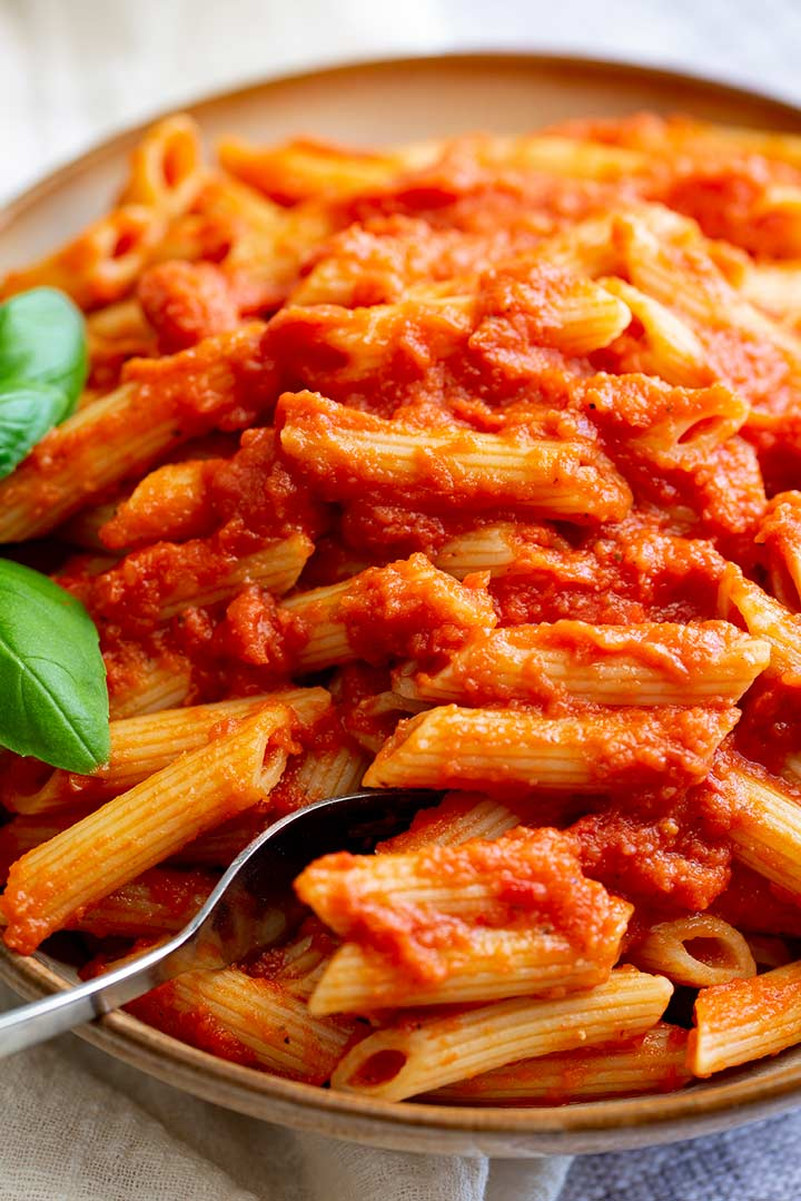 a fork sitting in a rustic bowl of pasta with a red sauce, garnished with basil