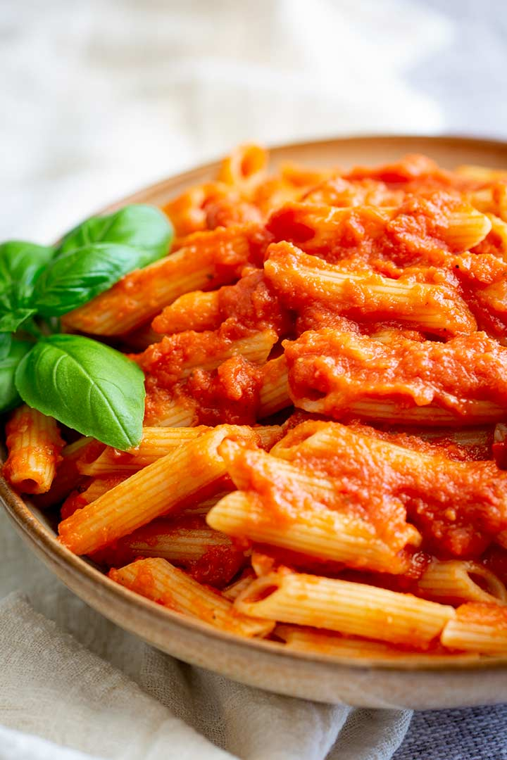 penne pasta and tomato sauce, in a light brown bowl on a grey table.