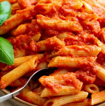 close up on a fork digging into tomato pasta
