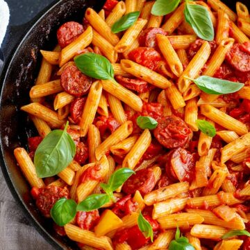 square shot of a cast iron skillet filled with pasta and garnished with fresh basil
