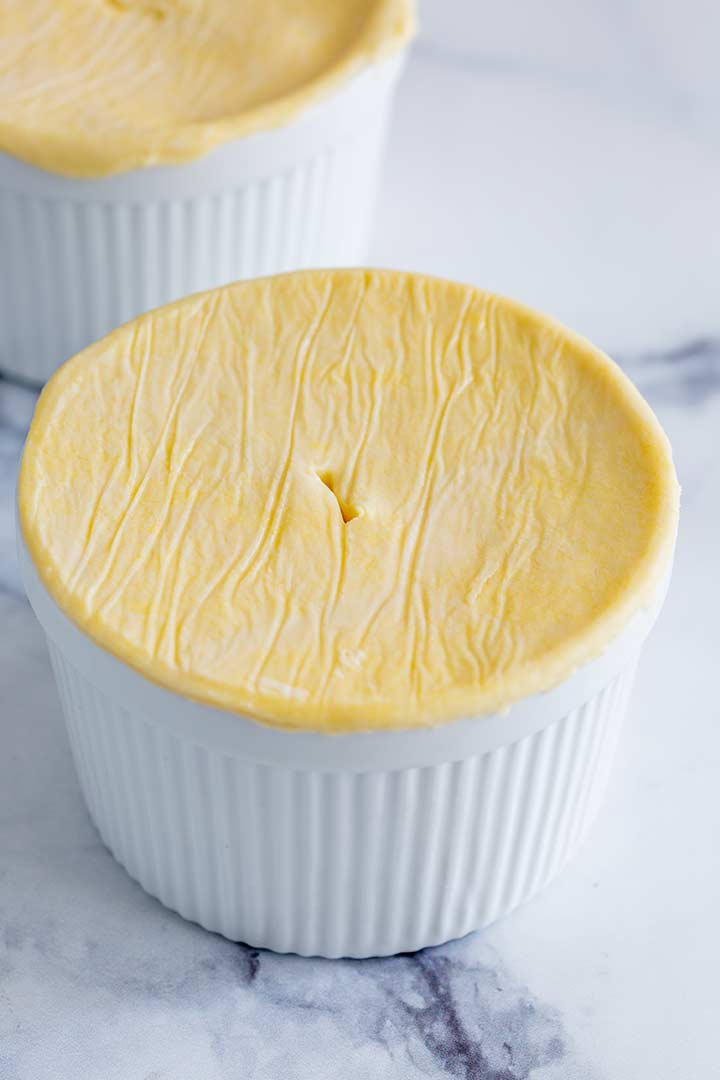 a white ramekin with a puff pastry disk on the top