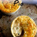 two pot pies on a metal tray, one with a spoon lifting out the fish filling with text at the top and bottom