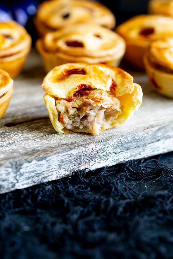 a mini pie with a bite taken out showing the sausage meat inside