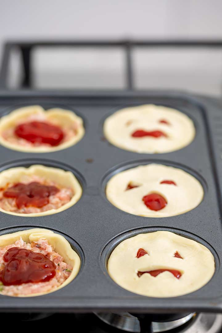 A muffin tin with sausage pies in the holes. Some have jack-o-lantern tops and some haven't had the top on yet