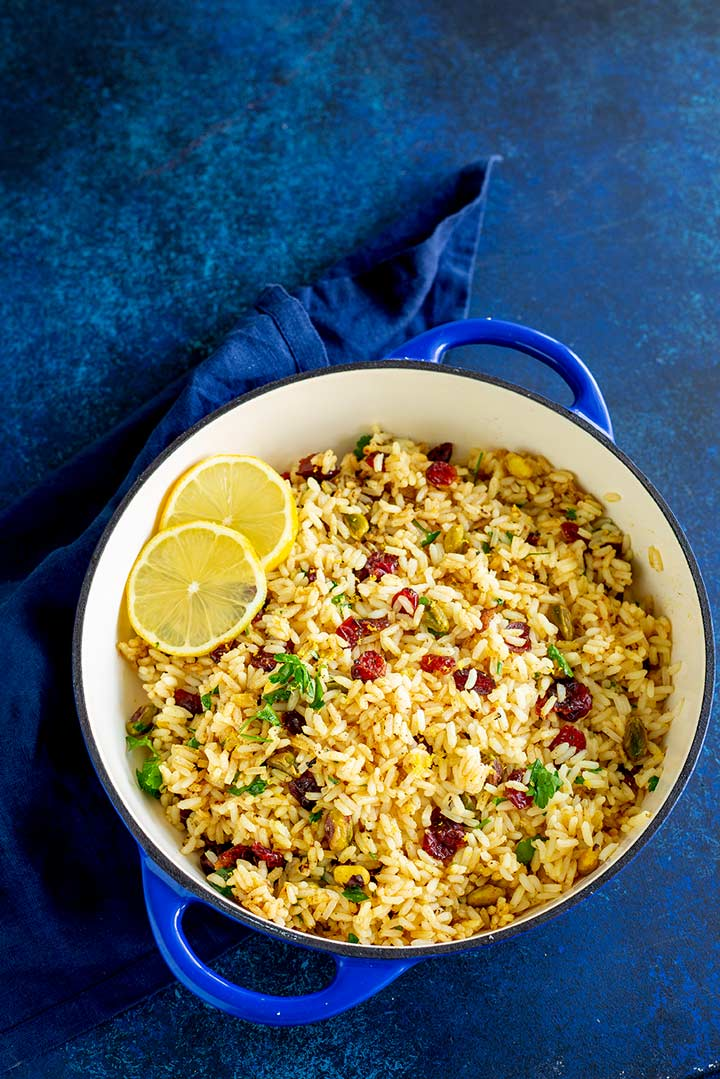 a blue pan filled with jewelled rice on a blue table with a blue napkin