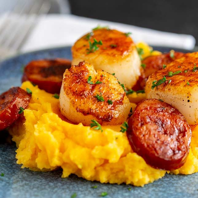 close up square picture of pan fried scallops and chorizo on a pile of sweet potato mash.