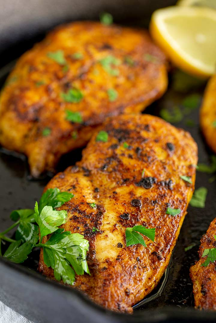 4 Persian Chicken breasts in a cast iron skillet garnished with parsley and lemon slices