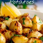 Greek potatoes win a white bowl with lemon wedges and text at the top