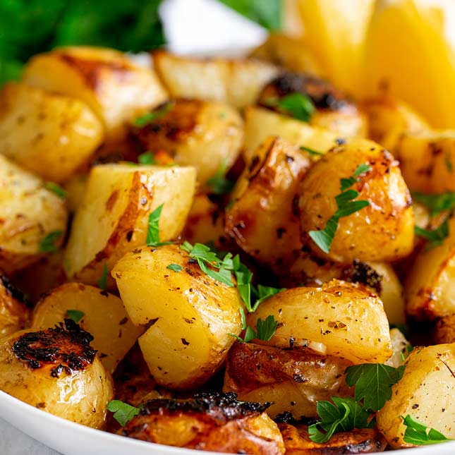Close up on roasted lemon potatoes in a white bowl