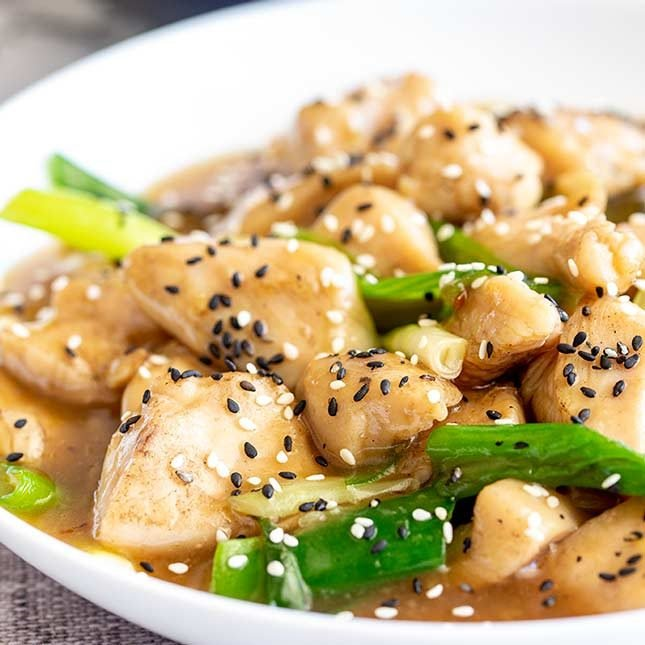 close up on stir fried chicken garnished with black sesame seeds