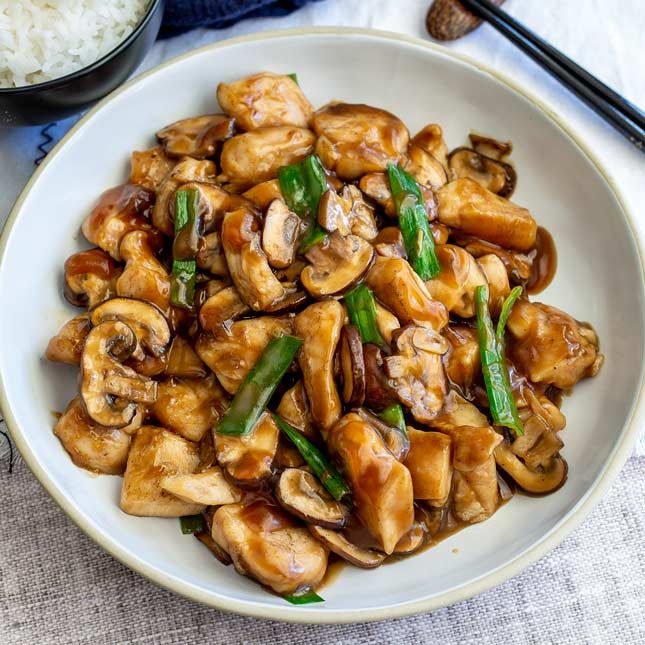 overhead view of a white bowl of Chinese chicken and mushrooms with green onions