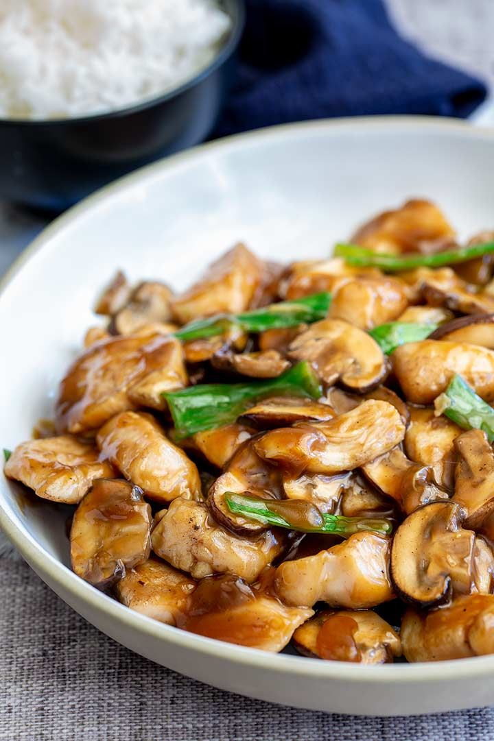 chicken and sliced mushrooms in a glossy brown sauce in a white bowl, with rice bowl behind