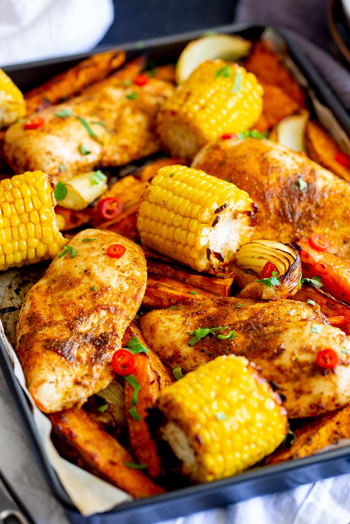 cooked chicken breasts, sweet potato and corn on the cobs on a metal sheet pan