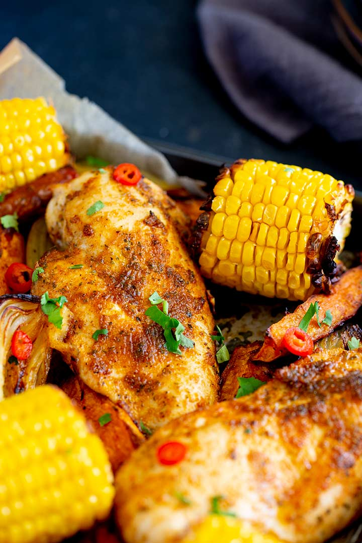 close up on 2 chicken breasts coated in peri peri seasoning in a tray bake with corn on the cob