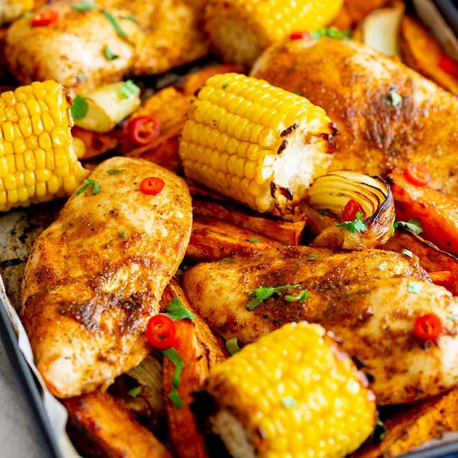 square picture of a peri peri chicken tray bake with vegetables and cili