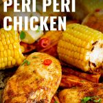 peri peri chicken on a sheet pan with veggies with text at the top