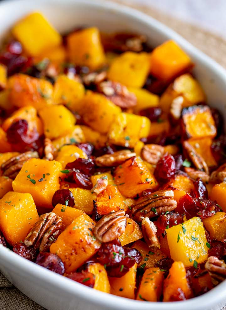 close up on a baking dish of roasted pumpkin garnished with cranberry, pecan and parsley