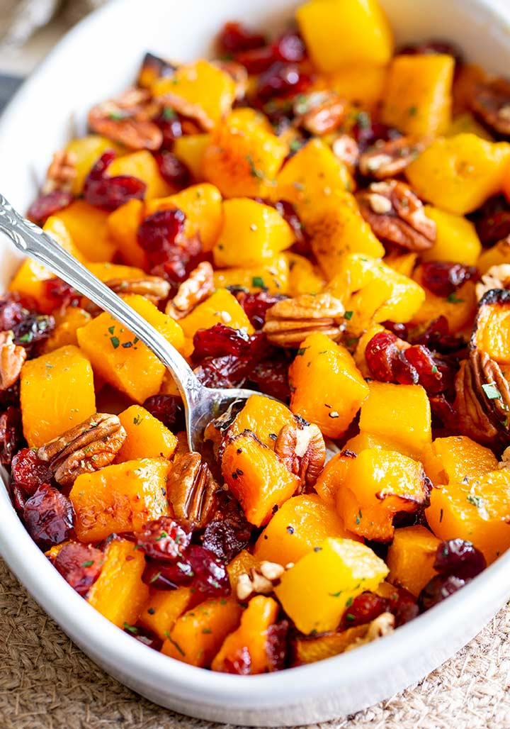 a white oval dish filled with pumpkin, cranberry and pecan with a silver spoon