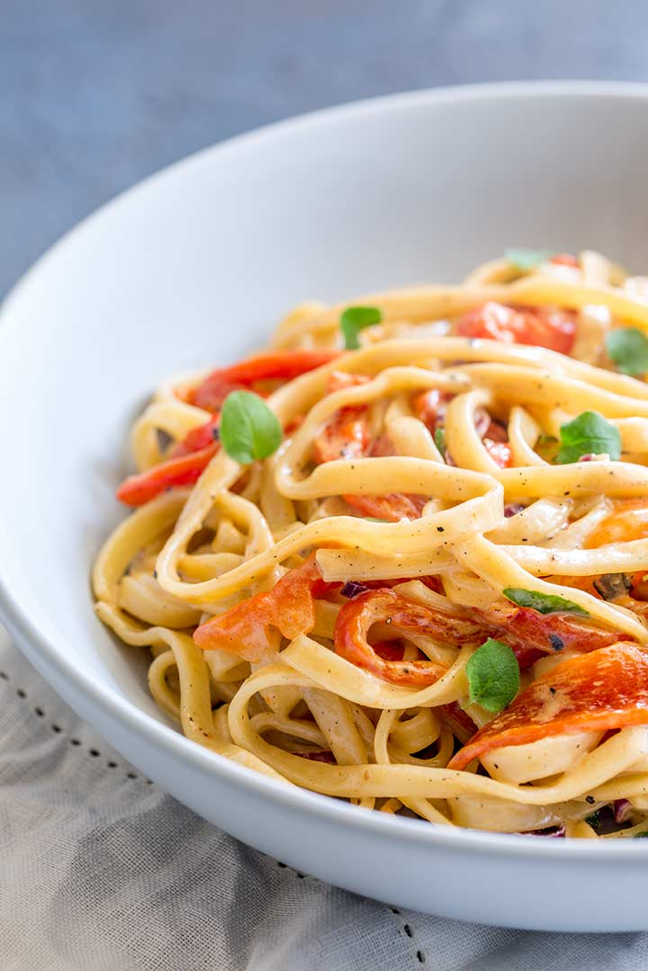 a pale blue bowl of red pepper pasta garnished with oregano on a cream linen napkin