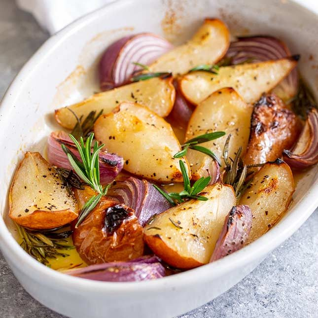 square picture of baked pears and onions in a white oval dish