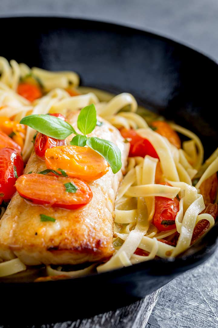 close up of a cooked fillet of cod on a bed of pasta with cherry tomatoes and basil garnish