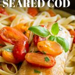 cooked fillet of cod on a bed of pasta with text at the top