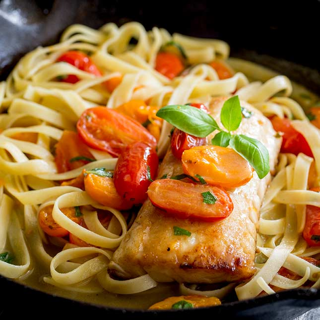 square picture showing a cooked cod fillet on a bed of tomato pasta