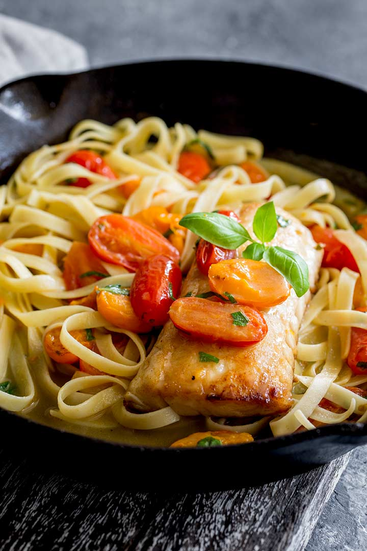 A cast iron pan filled with pasta and tomato with a fillet of fish