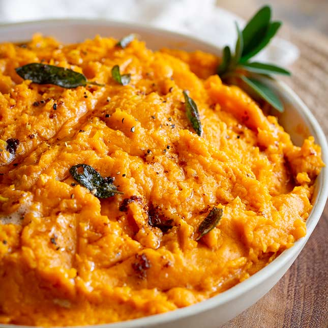 square close up photo of orange sweet potato mash garnished with sage