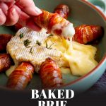 a hand dipping a bacon wrapped sausage in molten brie with text at the bottom