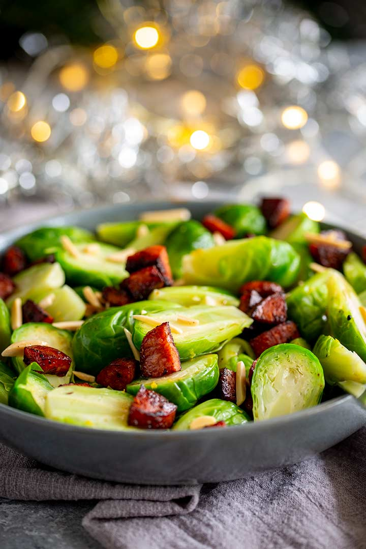 brussel sprouts in a grey bowl with fairy lights behind