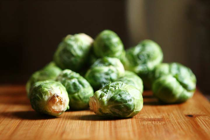 raw brussel sprouts on a wooden chopping board