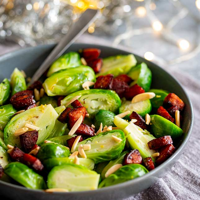 a spoon in a grey bowl of Brussel Sprouts with chorizo and almonds